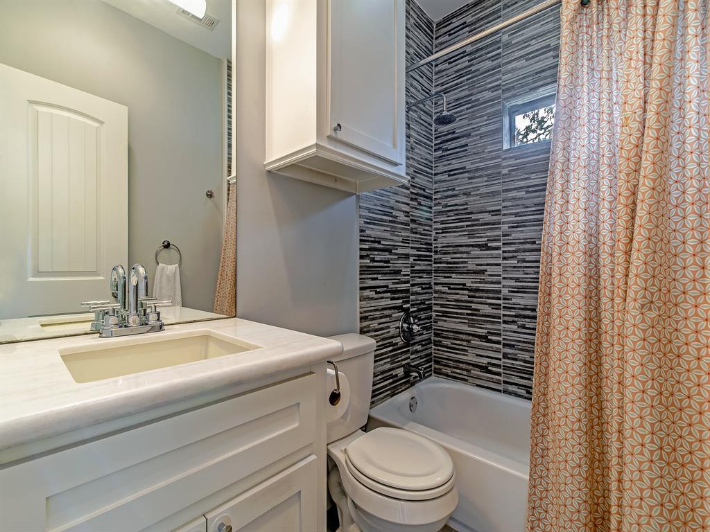 Hallway bathroom with decorative wall tile.