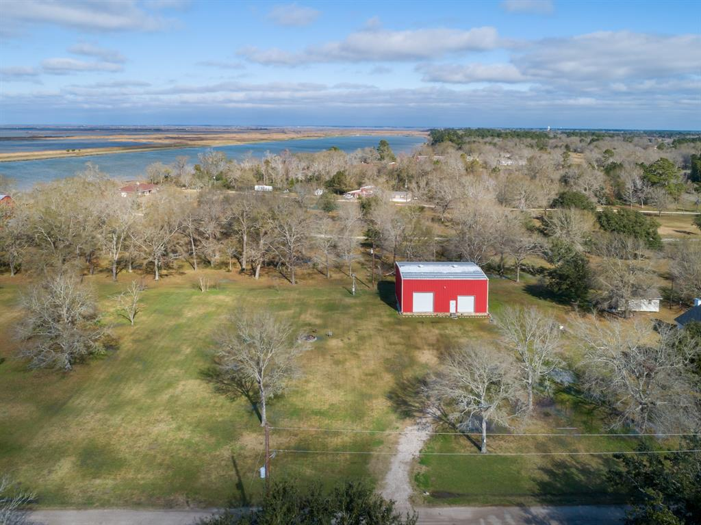 Looking to build your dream home in Anahuac? This great property consists of two tracts (1.1 acres) with views of the Trinity Bay and includes a 50ftx40ftx26ft, 2-story metal insulated building with (2) roll up bay doors on a 3 foot slab. The building is equipped with 24 hour surveillance camera, water, sewer and electric to supply the buildout to a barndominium, RV storage (hookup accessible) or shop and still have plenty of room to build your dream home on this gorgeous piece of property! Boat launch is 1/4 mile away.  Enjoy bonfires under the beautiful Texas skies with the concrete burn pit. A culvert and temporary driveway have been added for easy accessibility.  The property is located outside the Anahuac city limits, just minutes away from Galveston and Trinity Bay.  Also, just a 1/4 mile south of the Annual Texas Gator Festival.  This a hunters and fisherman's paradise.  Crystal Beach and the Boliver Peninsula are just a short 30 minute ride through the back roads.