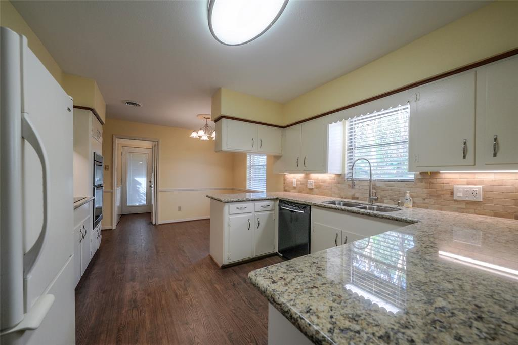 The kitchen has granite counter tops with a stone back splash. Beyond the kitchen is the breakfast area.