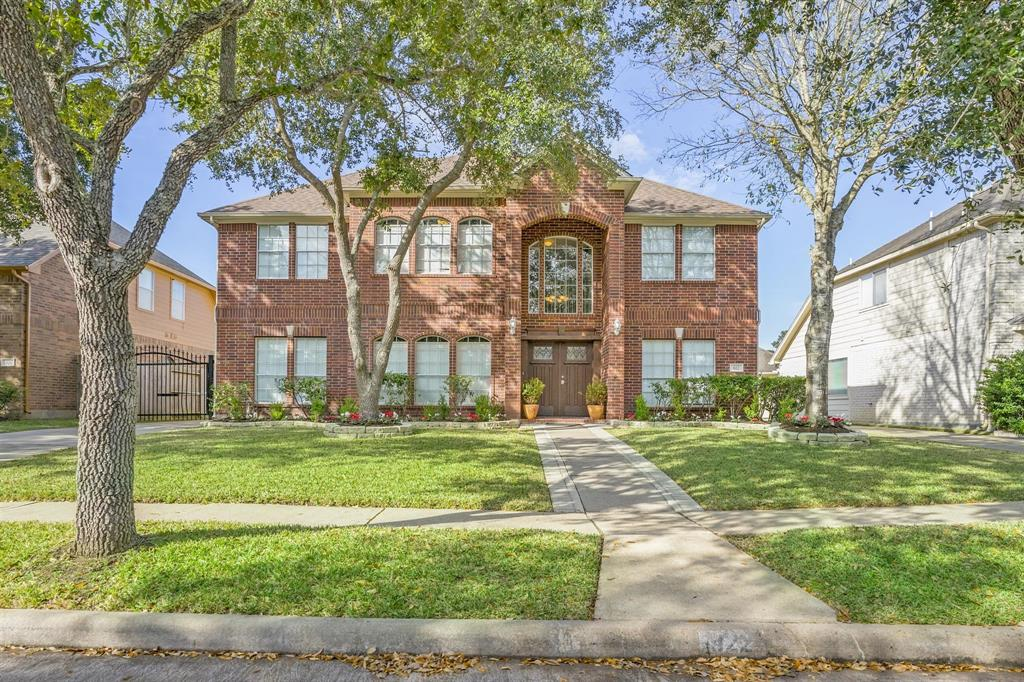 """NO FLOODING DURING HARVEY OR AFTER. LOW PROPERTY TAXES! EXEMPLARY SCHOOLS! NO REAR NEIGHBORS! REFRESHED LANDSCAPING! RECENTLY CHANGED ROOF! Beautiful upgraded 5 BED/4 BATH home in New Territory with GRAND FIBERGLASS DOUBLE DOOR ENTRY. Soaring two story high family room has a cozy fireplace wrapped with travertine to the high ceiling. UPGRADED custom kitchen with stainless steel appliances, over-sized custom ISLAND, GRANITE countertops, wet bar with WINE RACK, custom 42"""" upper cabinets, soft closing drawers and cabinets & pots/pans drawers in kitchen. Engineering WOOD and TRAVERTINE floors throughout, custom DRAPES, private gate in driveway, and sprinkler system! Beautiful staircase wrapped in engineered WOOD floors with large threads. 2 BEDROOMS with 2 FULL BATH downstairs. Both Formal Living and Formal Dining Room. Entire home was just recently repainted with fresh new colors. All drapes will come with your new home! NO REAR NEIGHBORS! BRING ALL OFFERS!"""