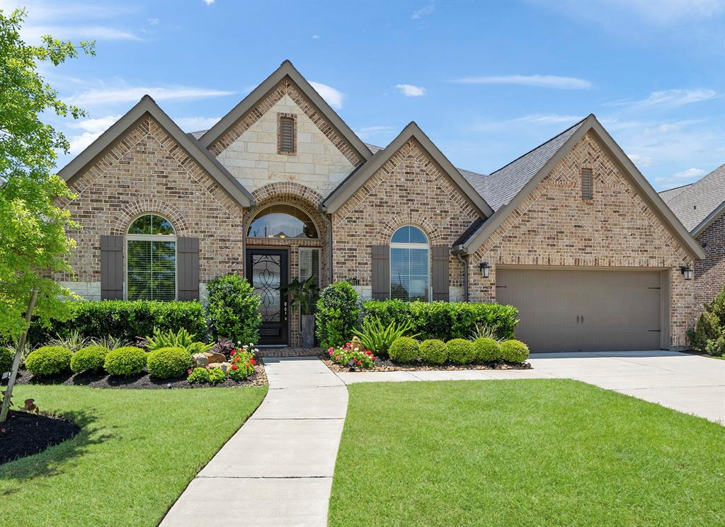 This home is equipped with EXTRAS added such as  HARDWOOD flooring in All BEDROOMS and MEDIA ROOM, WATER FILTRATION SYSTEM, DOUBLE OVENS, WINE COOLER, CUSTOM BUILT ENTERTAINMENT CENTER IN Media, EPOXIED GARAGE FLOOR, FRAMELESS GLASS on both WALK-IN SHOWERS, BATHROOM QUARTZ COUNTERS.  This is a 65' Homesite on Developer Retention Pond.  Impressive arched tiled entryway with 14' ceilings.  Oversized island with wrap around bar seating.  Views of outdoor living from front door.    HUGE OVERSIZED EXTENDED PATIO ON RETENTION POND with breakfast and formal dining areas.  This home has one hollywood bath with tub and quartz countertop and two Walk-In showers.   Surrounded by meandering trails, ponds provided by developer, beautiful community pool, fitness center and recreation.  Fantastic View.