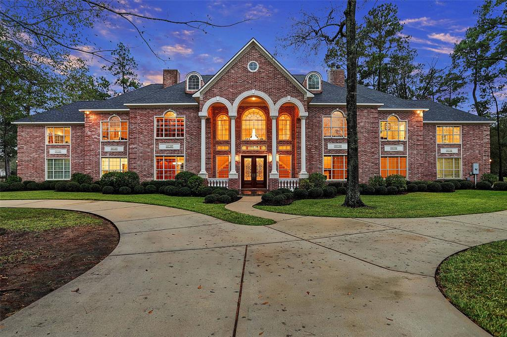 Stately and elegant, custom gated estate with pool (2018) is situated on a wooded 2.13-acre waterfront lot with scenic views of Lake Windcrest Golf Course. The home's wall of windows, majestic balconies and covered lanai provide magnificent views of a well-landscaped backyard, stunning pool and bricked patio ideal for entertaining guests. Mahogany double front doors open to a grand entry with a breathtaking double curved staircase & triple-tiered Swarovski Crystal chandelier. A beautiful kitchen with a massive island & 14' serving/breakfast bar opens to large, seamless living areas. Luxurious owner's retreat offers private balcony, fireplace & remarkable bath. Symmetrical private entrances feature art studio/classroom/office on east side & guest quarters w-kitchenette, living room, bed & bath on west side. Guest bed & study down, game room, library, amazing laundry & open living spaces make this a versatile home. Roof replaced 2015. NO FLOODING! 4-car garages. Exemplary Magnolia ISD.