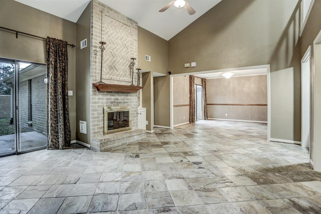 Living room offers slate flooring, floor to ceiling bricked fireplace and high ceilings.
