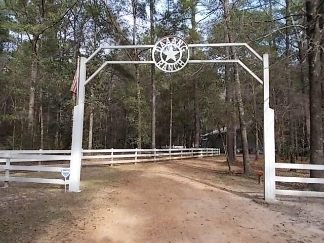 """Beautiful estate nestled on over 50 acres of heavily wooded land adjoining the Sam Houston National Forest. Featuring 4 bedrooms, 2 1/2 baths plus kid's """"secret room"""",  this property also includes a 2000 sq ft party barn with 2 half-baths and 1 full bath as well as a loft area which sleeps 12, a 2000 sq ft shop, pool, lush gardens, fruit trees, Koi pond, and creek. The house itself has an island kitchen with commercial grade appliances and granite countertops. The great room has a 2-story cathedral ceiling, fireplace and floor-to-ceiling windows. The master suite includes a sitting area, fireplace and access to the 1000 sq ft screened-enclosed porch. The property also boasts a greenhouse, garden shed, other out-buildings, whole-house backup generator and 3- 1000 gallon propane tanks.  If this property is not exactly what you are looking for,  it's """"Daaang"""" close!"""