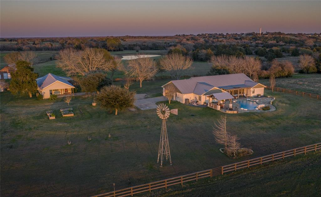 Impressive 77.77 acre ranch, with beautiful 2,945 +/- sq. ft. (per A.C.A.D.) 4/3 custom main home with a spacious open-concept living/dining area, wonderful kitchen, office, screened porch, impressive finishes and much more.  Also included is a 1,612 sq. ft. (per A.C.A.D.) 2/2 custom built guest house, with open concept living / dining and an attached carport.  Ideal for additional family and friends.  A vintage barn, charming windmill, several outbuildings and a handy workshop round out the improvements.  The home overlooks a gorgeous pool and hot tub.  A well-designed outdoor pergola frames the BBQ/cooking area and bar.  The multi-mile sunset views from the ridge are probably one of the most impressive features of the ranch.  There are pecan trees and several varieties of fruit trees in the yard as well as vegetable gardens just a few steps away.  The quiet, tranquil setting along with the excellent location and long views of the rolling countryside make this a must-see property.