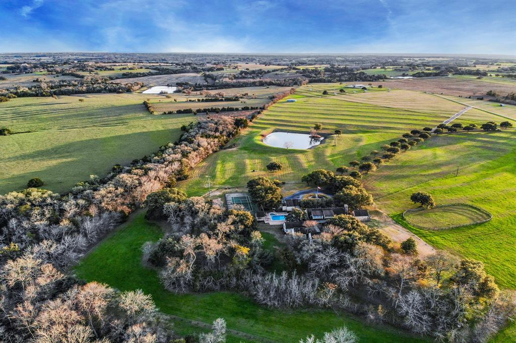 """When the automatic gate opens to Rolling Hills Ranch, you soon understand how this stunning property earned its name. The green fields gently rise and fall on the beautiful 60 acres of pristine pasture, meandering down a tree lined road to the 5,697sf home. The 4 bed, 4 1/2 bath home was featured in Veranda, praising the """"Truly Texan"""" proportions of the house, with a living room measuring 25 x 36 ft and a 28 ft ceiling. Kitchen has 2 Sub-Zero refrigerators, double ovens, Dacor gas range, 3 Bosch dishwashers and Sub-Zero wine refrigerator. Freestanding wine house, temperature and humidity controlled holds up to 2000 bottles is perfect for entertaining. Pool, spa, lighted tennis court, and expansive front/back porches for ultimate outdoor living. The bass stocked pond has a working windmill. Stable with 4 stalls, 2 offices and a circular riding pen. Agriculturally tax exempt. Conveniently located to Brenham, 78 miles from Houston, 90 miles from Austin and 44 miles from College Station."""