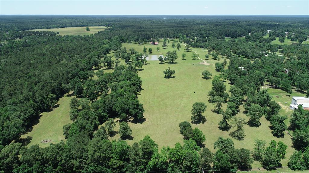 50.7 Unrestricted acres just a few miles east of Montgomery.  Beautiful rolling terrain.  South end is bordered by Bentwater.  About 500 feet of frontage on FM 1097.  Barn, cattle pen, ponds and water well on the property.  No flood plain. Ag exempt.  Additional adjoining 31.8 acres with two houses and barn available.