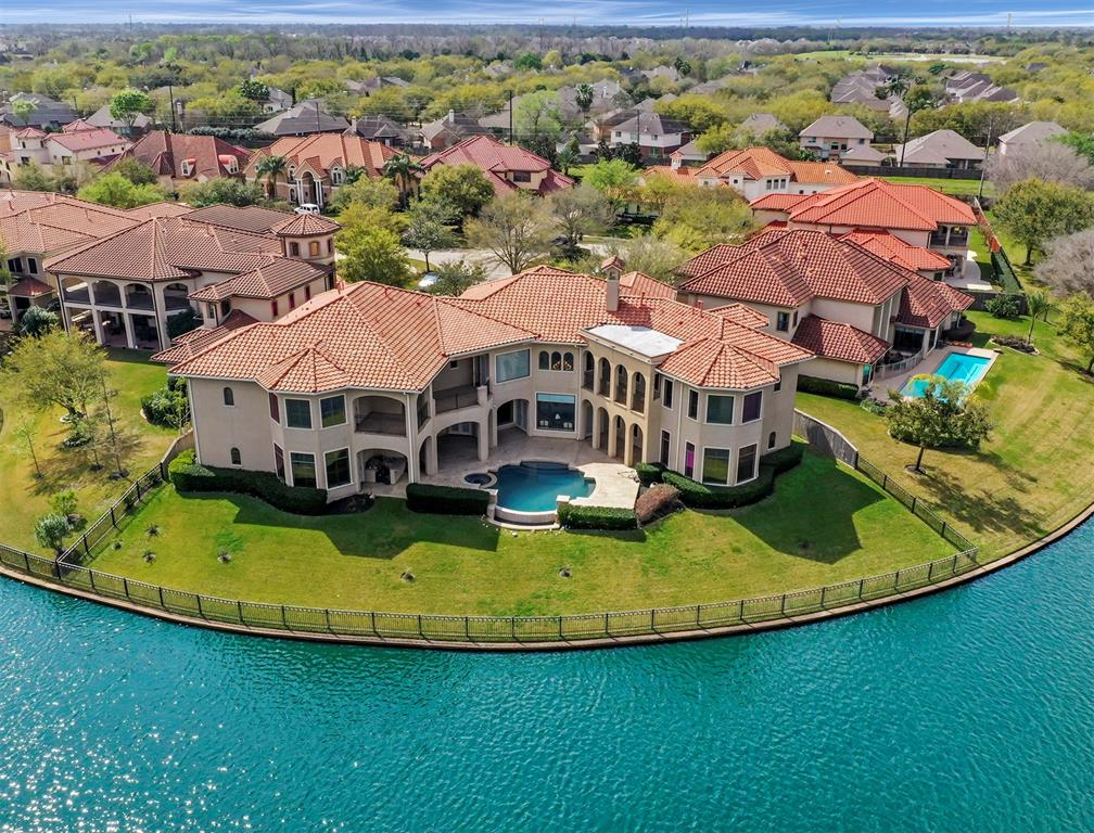 LUXURY ON THE LAKE! - AMAZING Executive home at end of cul de sac loaded with UPGRADES in the GATED section of Waters Cove in Riverstone. With 6 bedrooms(INCLUDING 4 MASTER SUITES!!) 6 full baths and over 8000+ sq ft of living space, this home is perfect for large families and multi generational living.   As you enter the home you are greeted with a grand entry and GORGEOUS tile flooring in all the main living spaces. The gourmet kitchen features high-end appliances, custom cabinets, a wine room, and a large wet bar.   The master suites each feature separate sitting areas and spa-like master bathrooms.  Head upstairs and you have your secondary bedrooms, game room and separate oversized media room and a flex room.  Step outside to relax on your covered patio and enjoy your outdoor kitchen, pool, spa and lovely panoramic lake views. Riverstone features resort-style amenities, top-ranked public schools and a prime location near shopping/dining and commuting routes...A MUST SEE!