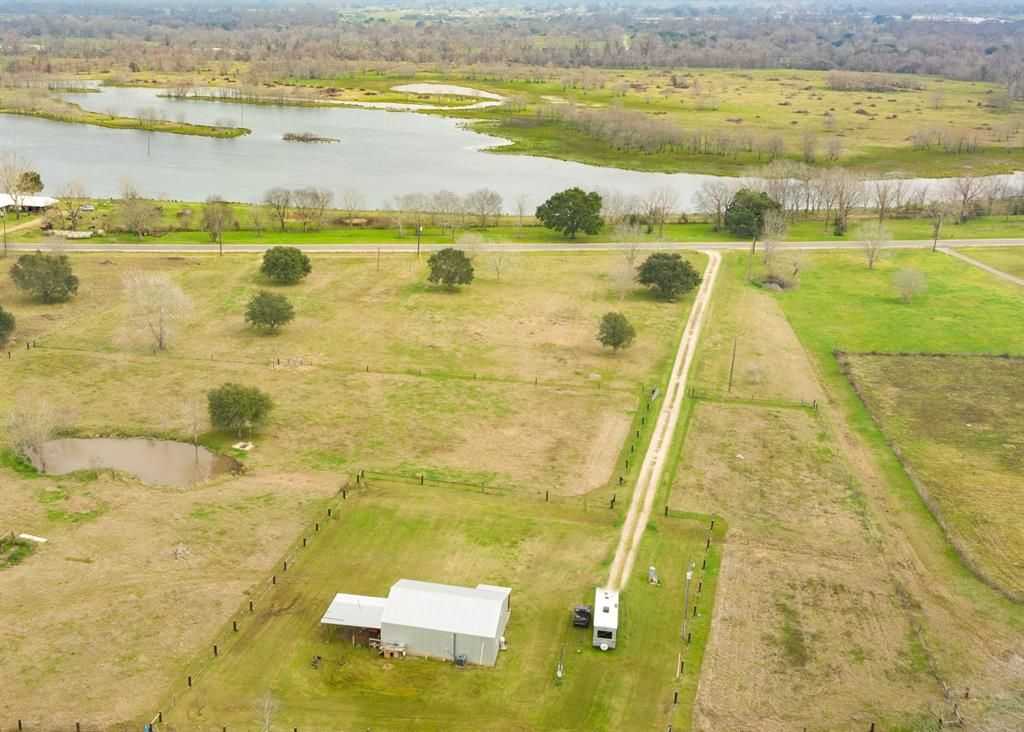Charming 10-Acre Ranch by FM 528, FM 1462 & Proposed TX-99 has 1/1/1 Barndominium, Ponds & Gorgeous Views of Coffee Lake. Property has ~287 ft Coffee Lake Dr Frontage & ~195 ft Old Coffee Plantation Ln Frontage (see plats). Centrally located between Angleton & Pearland about 20 miles away; Houston & Freeport about 35 miles away. Several mature oak & pecan trees scattered throughout cross-fenced green pastures with plenty of room to build larger home. Quiet community surrounded by lakefront properties & ranches with custom built homes. Bring your horses & spend nights gazing at twinkling stars. Great location close to TX-288 & FM 521 makes commuting a breeze to Downtown Houston, Texas Medical Center, Hobby Airport, Freeport Plants & Gulf Beaches. TX-99 is proposed to cross TX-288 at CR 60 about 10 miles NE of the Property (see map). Perfect for country living with horses, producing hay/crops, and raising livestock & poultry.