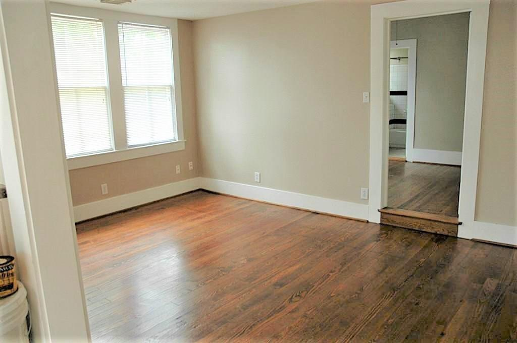 The living room is spacious with generous wall space. The door to the right leads to the bedroom and bath.