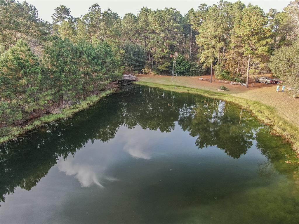 This is truly a RARE FIND! 7+/- Acres of Unrestricted Property in Conroe with TWO houses + an AMAZING stocked private pond/lake! Located just off of I-45/Crighton Rd and FM 1314; NO flooding! So many possibilities-make this your private estate, build your business or do both! The property offers a pristine fishing pond stocked w/bass, perch, catfish. Picturesque scenery w/bridge, pre 1941 windmill, curio building dated back to 1934 w/local history that was relocated to this spot, 24x27 metal workshop, 2 private well + right-of-way into River Plantation! Main home has been loved by ONE family EVER! The circle drive leads to a well-kept home boasting a spacious living room w/FP + game room equipped w/a ceiling fan from the Texas/Pacific railroad station in Dallas! The kitchen is light/bright w/solid wood cabinets, solid surface counter top + large dining room w/bay window. Master bedroom + 2 additional beds down. 4th bedroom w/bath is the only room up. 2nd Home is 3/2/2 w/great updates!