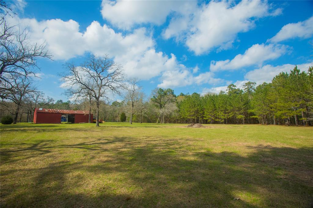 Mostly cleared, this property is ready to build your dream home. Close to the new 249 loop (Aggie HWY), this 4.46 acre property combines country living with convenient commuting. Enjoy the beautiful pine trees in the back and front.  A trail runs along the back high fence. Red barn and a fenced vegetable garden area are also on site. Listed at lot value. There is a well and septic in place, but have not undergone testing and inspection yet. Testing at buyer's expense.
