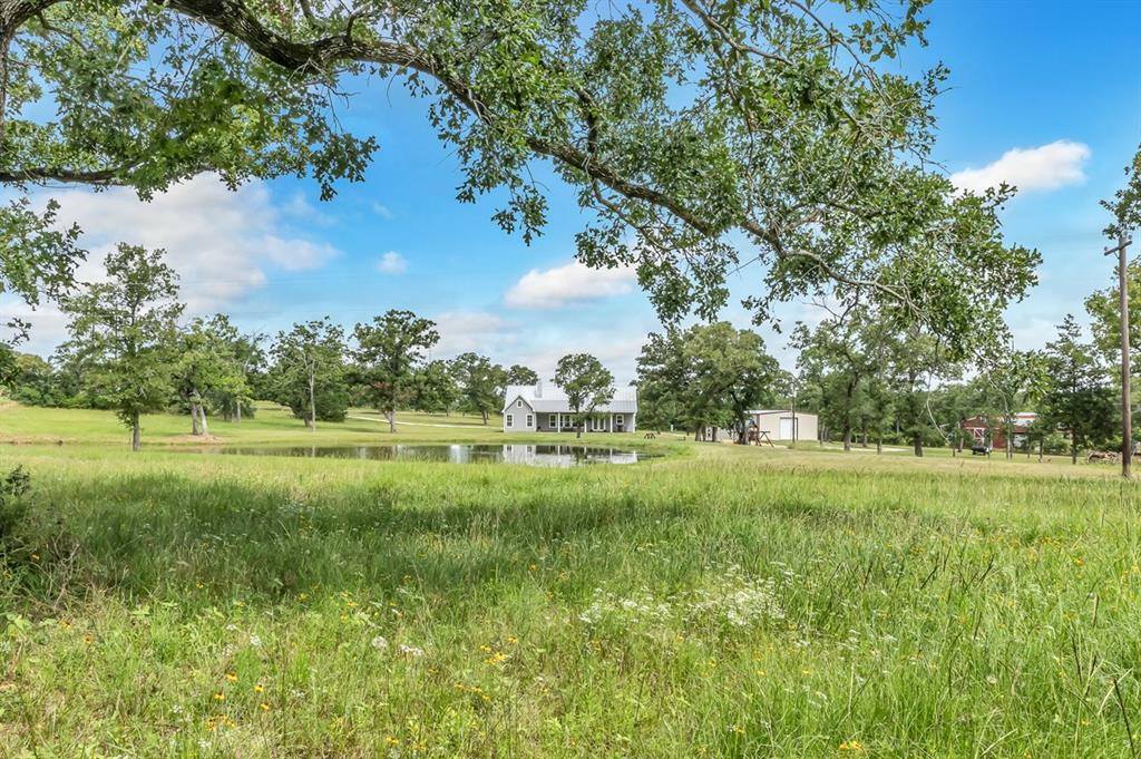 Wonderful Texas Farmhouse on a sprawling 11 acres just minutes from south College Station and Texas A&M. The 2,382 SF home, complete in 2014, offers three bedrooms, three baths and a spacious living, dining, kitchen area with bead board wainscoting, a wood burning fireplace and windows spanning across the room filling the space with light and affording views of the grounds. The wide porches across the front and back of the home welcome a place for outside entertaining or space to just sit and enjoy.  Other features include: a 2,000 SF metal building fully equipped with a kitchenette and bathroom, a 20' overhang and 12' drive through, roll up doors, a half-acre stocked pond, rolling terrain, scattered oaks and sandy-loam soil. With great access to College Station or Houston, this could be a full-time residence or weekend/gameday ranchette.