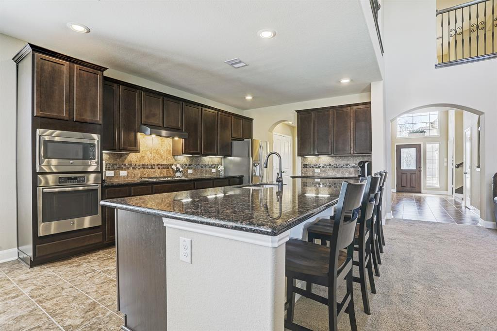 Stainless steel appliances and large kitchen island with seating.
