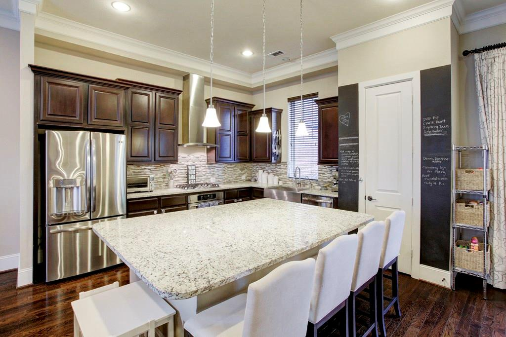 A granite island & breakfast bar anchors the open style kitchen which features high end GE Profile stainless steel appliances and deep single compartment farmhouse sink!