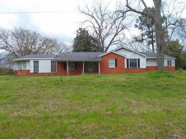 Great location less than a mile from Loop 304 on State Highway 21 East. This three bedroom 2 bath house features over 2,000 square feet of heating and cooling. Some of the features are a large kitchen, breakfast area, dining room and a living room. You will find some of the original wood floors in the house along with large bedrooms and decent closet space. The current owners started a renovation on the house but have decided to let someone else put their own touches to the property. Outside you will find some of the most majestic tree including a large magnolia that is in the back yard. There is a covered patio perfect for outdoor living area along with a two car detached garage. You will also find 5.58 +/- acres of land that is mostly open with a great barn or workshop on it. Come see what all this property offers!
