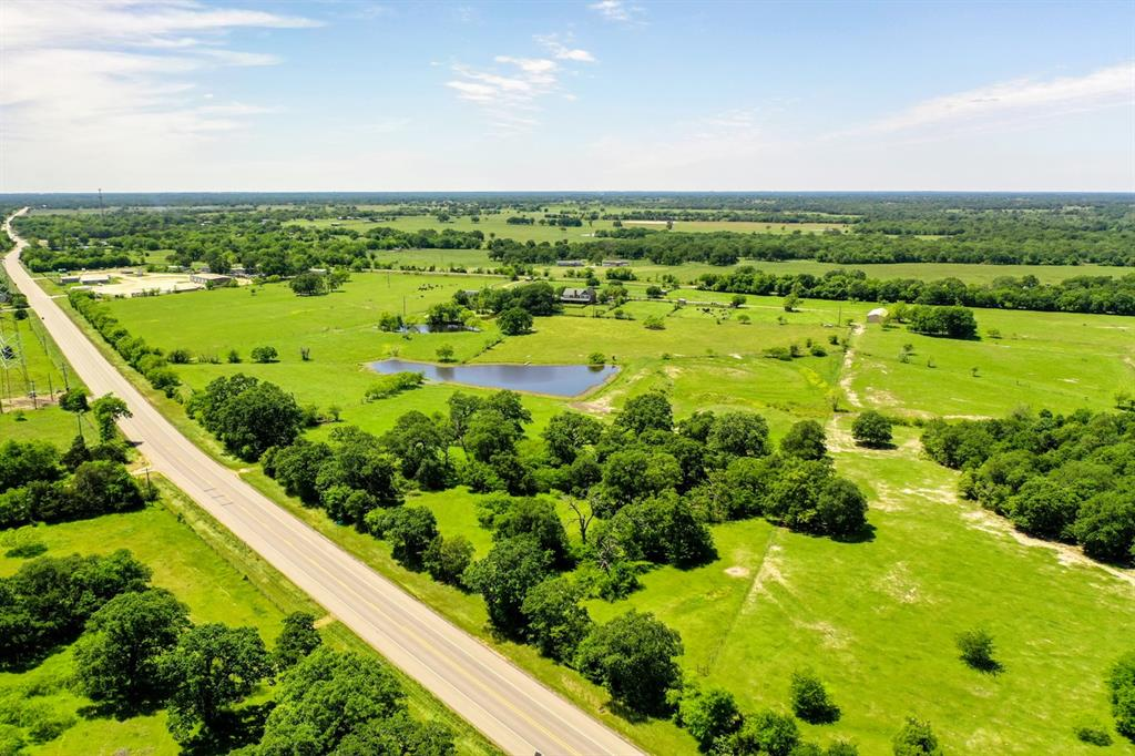 """11+/- Acres of the perfect homesite in Madison County just came available for your dream home! Picture your family on their own piece of Texas land with endless possibilities.  This country acreage is on the outskirts of Midway only 10 minutes from the city.  The property features 1150 ft Hwy 21 frontage.  Maybe you want to office from home or just the convenience of a well maintained highway in the country.  The 2 acre fishing pond is sure to bring you lots of joy  while relaxing with friends and family competing for the """"big one"""".  Improved green pastures and beautifully matured oaks make for plenty of sites to build the house you've been dreaming of.  Additional acreage is available.  This land is located 10 miles from I-45 in Madisonville, 95 miles from Houston and 150 miles to Dallas. The combination of location and beautiful land just made this the perfect investment for your future.  Call for your tour!"""