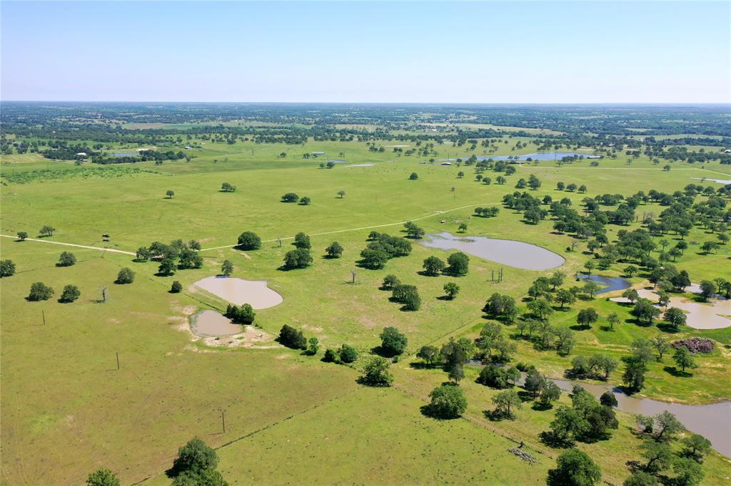 Cattleman, horseman & dog trainers dream property! This 207.576 ac is less than 20 min from town & primed to suit your needs w/5 ponds (3 stocked), barn, shed, corrals/gates/chutes, Lee Co. Water & 2 water wells (1 hand dug/1 drilled), aerobic septic, electricity & phone on property. 100+ yr house used as shop/storage. Level, open pastures w/Post Oaks scattered throughout. Pomegranate & Crepe Myrtle trees by previous homestead. Active mineral lease. No minerals. Non-realty farm equip for sale separately.  Acreage includes PID 17638 & 85464. Call to schedule a showing today!