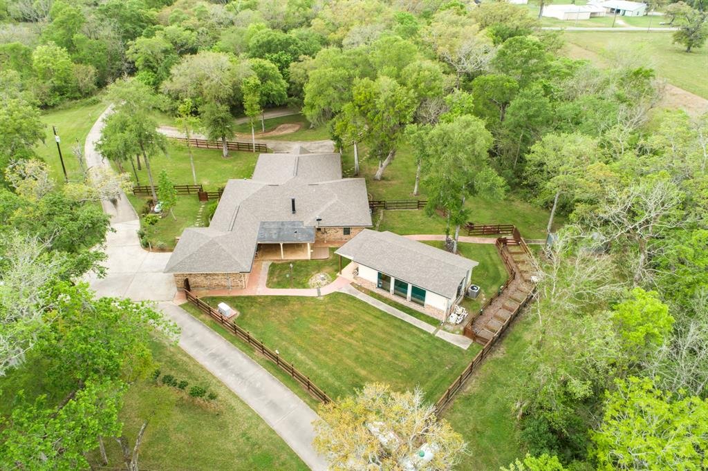 Beautiful setting on 24.9 acres of land with electric entry gate. Over 1100 feet of concrete drive way from entrance to house with extra circle driveway in front of house and to shop several hundred feet back of the house. It has 2 ponds, one 13 feet deep and stocked with good fish. The home with 4 bedrooms, 3 baths and granite counter tops. Has alarm system and good generator. There is a n enclosed pool just back of house with central ac and heat plus large screen TV and 1/2 bath. The 2100 sq. ft. shop has central heat and AC and also has a good generator, air compressor and full bath. There are 6 security cameras, 2 aerobic septic systems only 6 years old, one for the house and one for the shop, each one is 250 gal. 500 foot water well. There is 9 acres that you can bail hay. A deer stand behind pond and red lights in the edge of woods for night hunting. Garbage pick up once a week. No water in Harvey, no water anywhere close. Located in zone X of the Fema Flood plain.