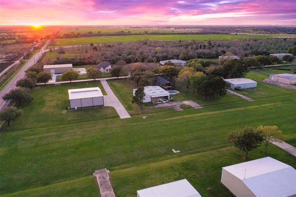 Built in 2018 this 5600 sq ft (80 X 70) Hanger is located on 1.7 acre runway lot in Fort Bend County's Covey Trails Aviation Community. Prime corner lot on runway, no need to taxi! Stained concrete floors, RV hookups (temporary), two split ACs, electric water heater, huge state of the art fan, full bath with seamless glass shower, 2 overhead doors; one is approximately 60 ft wide.  Pilot's Control Tower office/lounge upstairs. Great contemporary design!  There is still plenty of room to build a home on front of lot facing beautiful mature oak tree lined street.  Runway is 3300 X 100 and sod surfaced, 130' elevation, airport is open to public, and hosts community events.  A great opportunity for an aviation enthusiasts, belong to a community that shares your passion for flying!   Seller has geotechnical studies, survey and architectural plans to share with buyer.