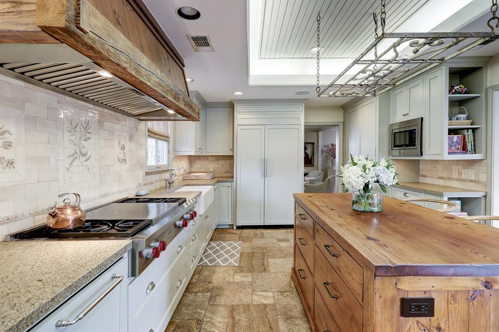 Custom hand glazed tile backsplash, built in Kitchen Aid Refrigerator and dishwasher both replaced in 2019. Raised ceilings along with recessed lighting open up the space.