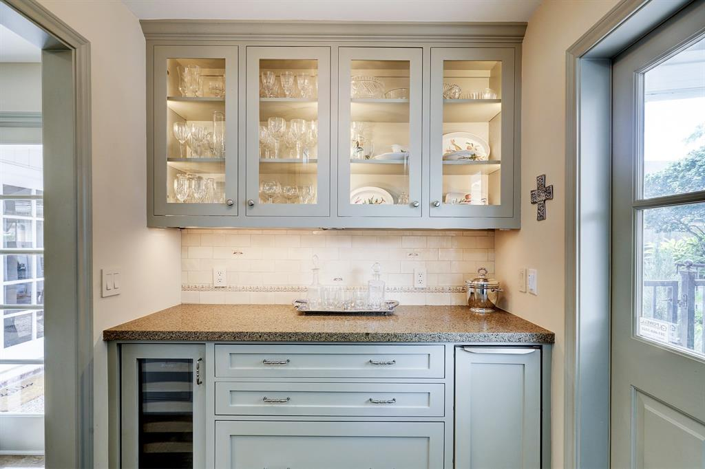 Bar area is just off of the kitchen. Built in whirlpool ice maker and wine fridge make for a great setup. Lighted cabinet perfect for displaying barware.