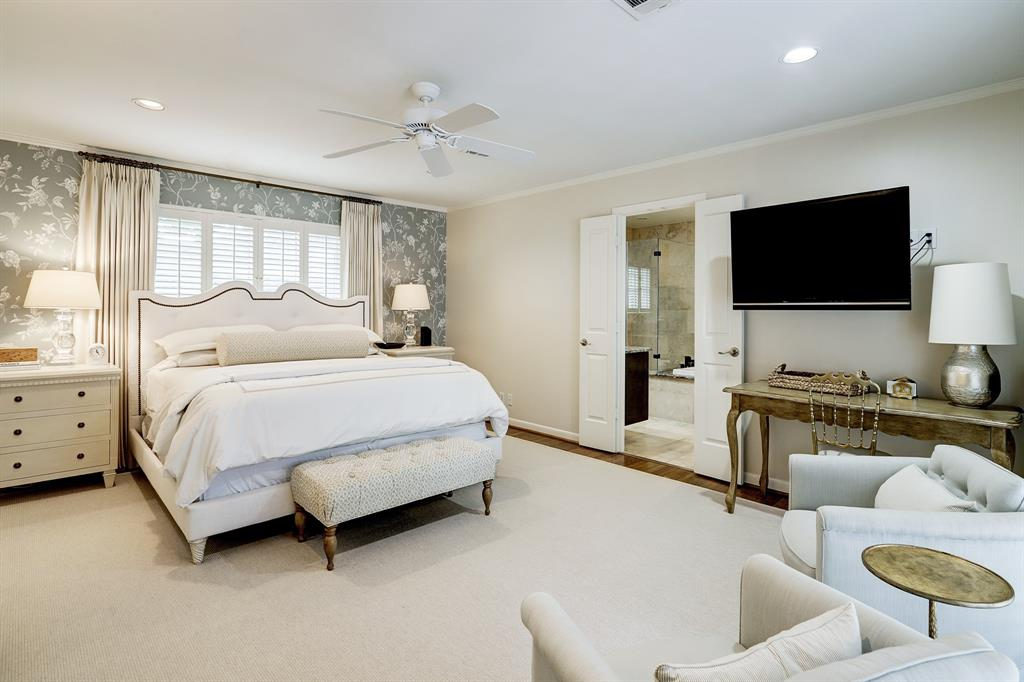Relaxing master bedroom features neutral paint, recessed lighting and a wallpapered wall. Wood floors are continued throughout the home and hallway.