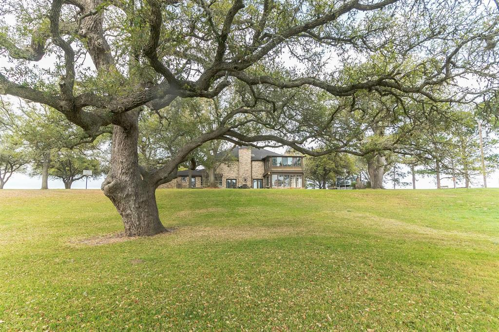 Beautiful updated brick 5/4, 5,066 SF home on 15+ acres. 2 miles from Hallettsville, Lavaca River frontage at back w/massive live oaks. 3 car garage. Formal entry, sunken family room w/wood beamed ceilings, stone fireplace, built-ins, wet bar/fridge. Large updated island kitchen, beautiful granite countertops, SS appliances, tons of cabinets, walk-in pantry, large casual dining area. Formal dining, spacious master bedroom with large en suite, office, sunroom, laundry room & bonus room off dining room. 2nd floor w/large second master bedroom w/sitting area, fireplace, built-ins, huge en suite & enormous walk-in closet. Also on second floor are three oversized bedrooms, a fourth bathroom, sunroom, second laundry area for the upstairs. Natural light drenches the inside & quality consumes this updated property w/beautiful tile floors, recessed lighting, wainscotings, crown moldings, updated utility & lighting fixtures, built-ins & granite surfaces throughout are just a few of the extras!