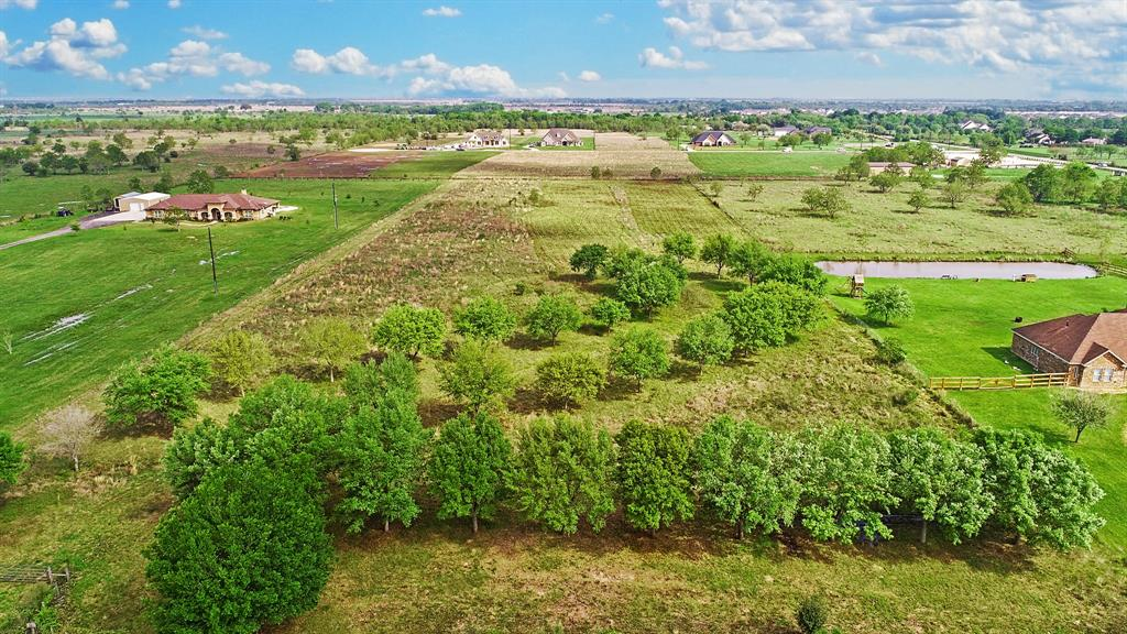 "This property is truly a gem on the Katy Prairie. The neighboring lots are developed, and still do not possess the established Oak grove that this property includes. Planted and maintained by hand for 15 years, these trees are the center point of this incredible nearly 7 acre lot. If you want to live IN Katy, but have the ability to live a ""farmstyle"" life, this is a wonderful option."