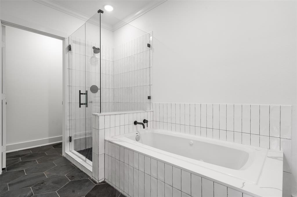 The finishes in the master bath include hex tile floor, subway tile tub and shower surround and modern glass shower enclosure.