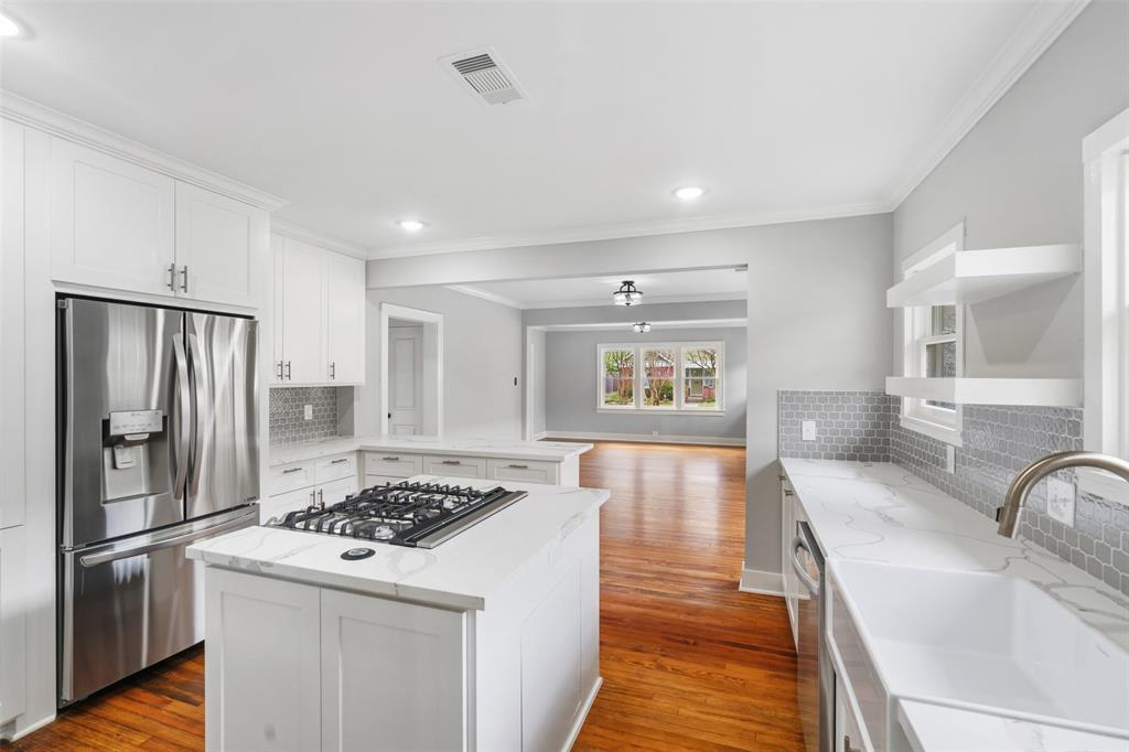 The kitchen features custom cabinets, quartz counter tops, mosaic tile back splash and stainless steel appliances.