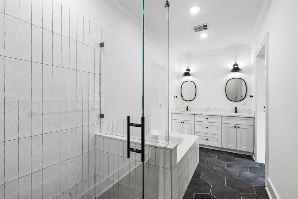 The modern master bath features dual vanities and separate tub and shower.