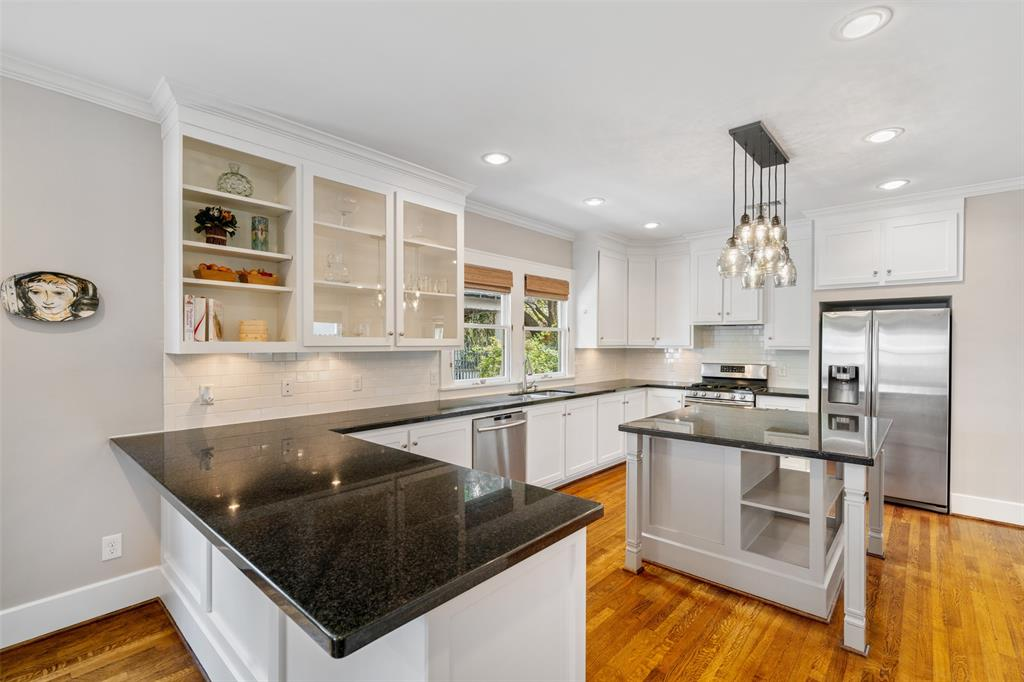 The kitchen also includes stainless steel appliances, including a gas range, and subway tile backsplash.