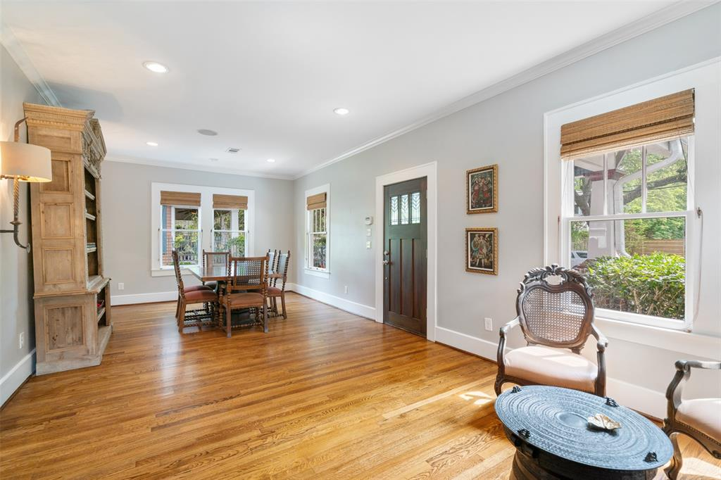 Your guests will be welcomed into this large receiving area. The space to the right is currently being used as a dining room, but this space is very flexible.  This room, like most of the house, includes gorgeous oak floors, recessed lighting, crown molding, and like the front porch is wired for sound through the Home Automation system.
