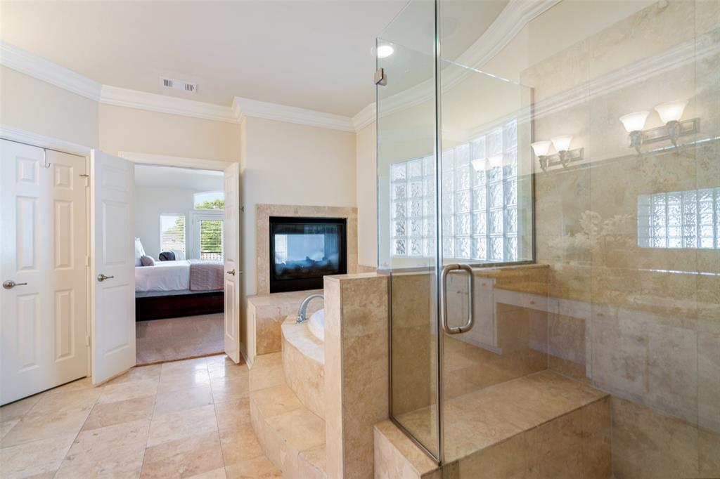 The double-side fire place faces the tub in the master bath
