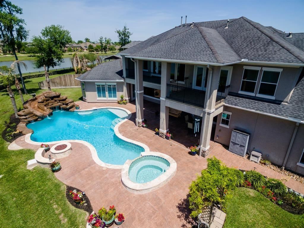 Stunning, custom-built home on over 200 ft. of water frontage! This spacious home features 5 bedrooms, 5 baths, a 6-car garage, heated pool & spa and high-end amenities throughout... hardwood & travertine flooring, automated Hunter Douglas window shades, plantation shutters and more. The amazing chef's kitchen boasts custom cabinetry, granite counter tops w/ travertine backsplash, Wolf gas cooktop, built-in refrigerator, separate ice maker and a wall of windows overlooking the backyard oasis.  The master suite features two walk-in closets & whirlpool soaking tub. Upstairs, the home offers a second living area with adjoining game room, home theater, a climate controlled storage room & two balconies w/ panoramic waterviews.  The one-of-a-kind, 6-car garage touts two auto lifts, high ceilings, tandem-depth ports & additional parking space in the gated side drive... an amazing opportunity for an auto or home workshop enthusiast and something you are not likely to find anywhere else!