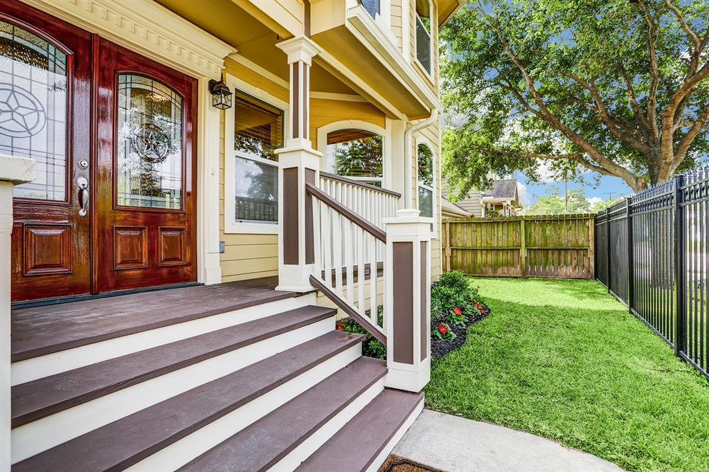 Beautiful double doors with detailed millwork and wrought iron fence.