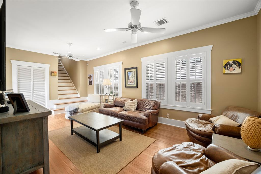 The second living/family room readily accommodates big, comfy furniture.  The windows overlook the driveway and the stairs lead to the primary bedroom suite.  The plantation shutters are one of a number of thoughtful upgrades added by the current owners.