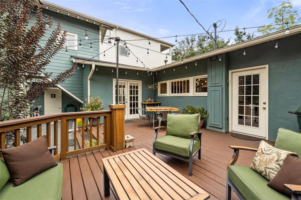 The well designed deck leaves lots of space for lounging and dining furniture.  The double doors lead to the second living/family room.  The white door and wall add privacy to this space from the driveway.