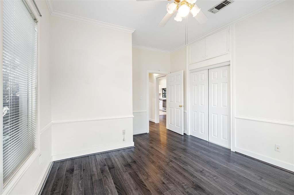 One of two bedrooms that includes ceiling fan and laminate flooring.