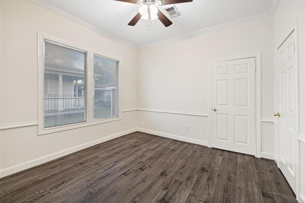 Another bedroom with ceiling fan and laminate floors.