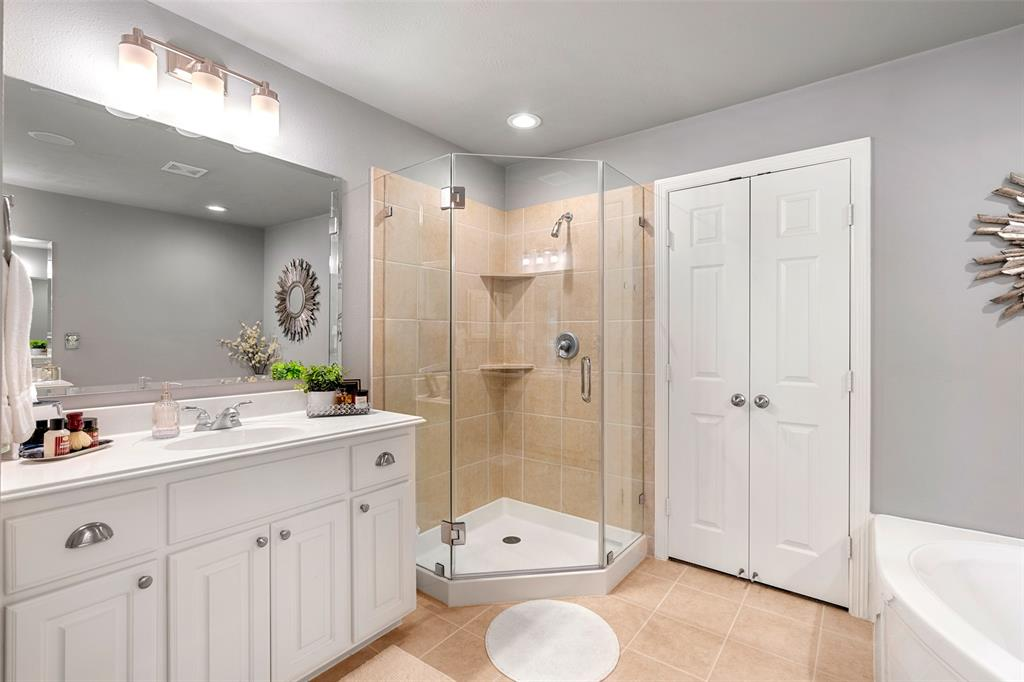 The master bath also features a separate shower with modern glass enclosure.