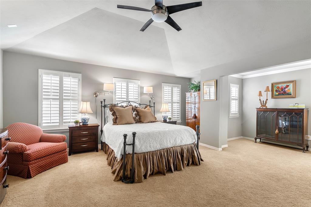 The master suite features a vaulted ceiling, plantation shutters and a spacious walk-in closet.