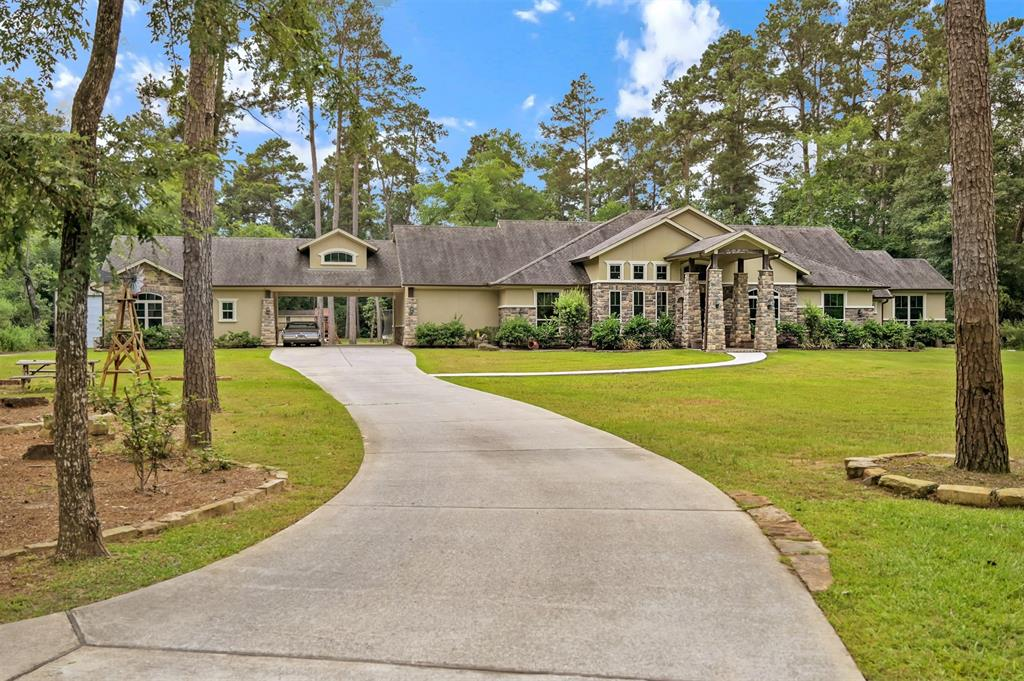 Rare find! This highly attractive gated home sits on an amazing 5 acres. Property is fenced and in a highly desirable location just outside of The Woodlands. Low taxes and HOA! Home comes with oversized 36x64 storage building to store your RV, Boat, cars, etc. This home has it all - heated and cooled saltwater pool, solar panels, outdoor kitchen and so much more to make this home your perfect retreat. Spacious open plan with top of the line kitchen. Home has beautiful wood beams, crown modeling and custom lighting fixtures.