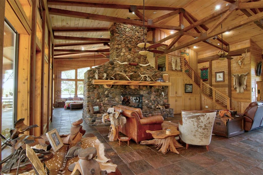 Featherquest - Delightful country lodge with separate guest quarters in the heart of 93 rolling, unrestricted acres overlooking a pristine fishing lake. Set on a hill among mature live oaks, the 4,470 SF residence offers wide covered porches with views of the 10 acre lake. Inside, a massive two-sided river-rock fireplace soars through the pine rafters to the two-story aspen ceiling. The kitchen features a huge u-shaped island with breakfast bar, hickory cabinetry, 6-burner Wolf gas cooktop, Sub-Zero refrigerator, double oven, & a walk-in pantry with aromatic cedar ceiling. Slate floors, cedar walls, & large windows for natural light. Guest bedroom upstairs. 2,000 SF extra room has been used for dog training but could be adapted to many different purposes.  Hot tub surrounded by multi-level decking. Ag/Timber exemption in place. Located just off HWY 21  between Crockett & Madisonville, this prime country estate offers easy access to the Houston area as well as DFW.