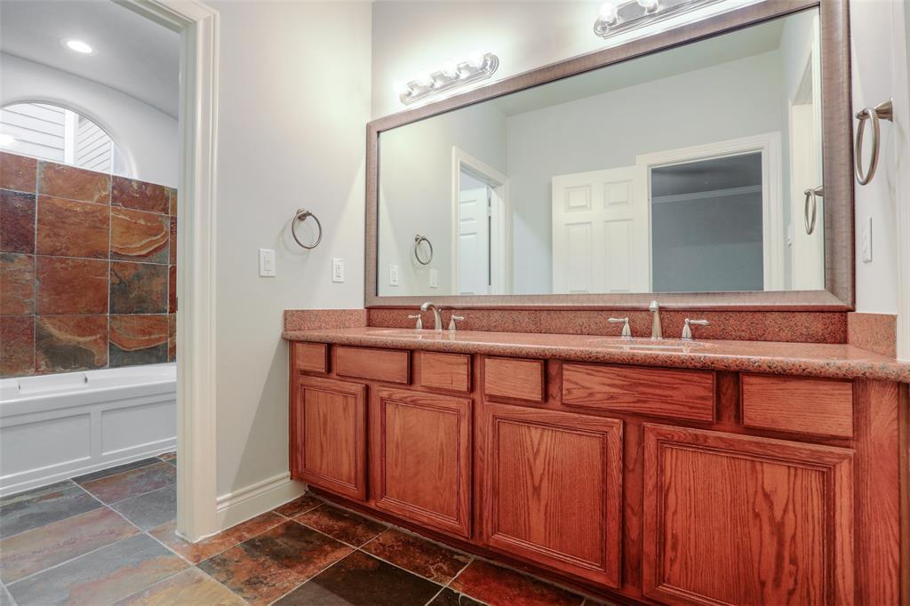 En suite bathroom with double sinks and garden tub.
