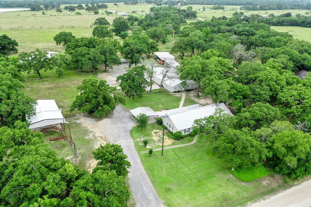 Incredible 3/2 ranch home with guest/rental cabin on 5 immaculate acres won't last! Need space to spread out, tinker, and live that country dream? Get your party list ready cause a big gathering is just what this place is made for. The welcoming porch and yard lure your jealous family in for a peek. Notice the huge cedar beams that tie your plus sized kitchen/dining/living room together with custom cabinets and room for the masses. Your favorite spot maybe the bonus loft upstairs, the breezy screened in porch, the 150'x300' lit riding arena or one of the many metal barns. Horses and livestock will live comfortably in their space that blends nicely with the landscape. The well insulated shop is built for business with 3 bay doors and a separate office space.  Freshly installed aerobic septic and water well complete the updates on the property. This a hidden gem is only a mile from I-45 in Madisonville putting it 140 miles from Dallas and 90 miles from Houston. Don't delay, call now!