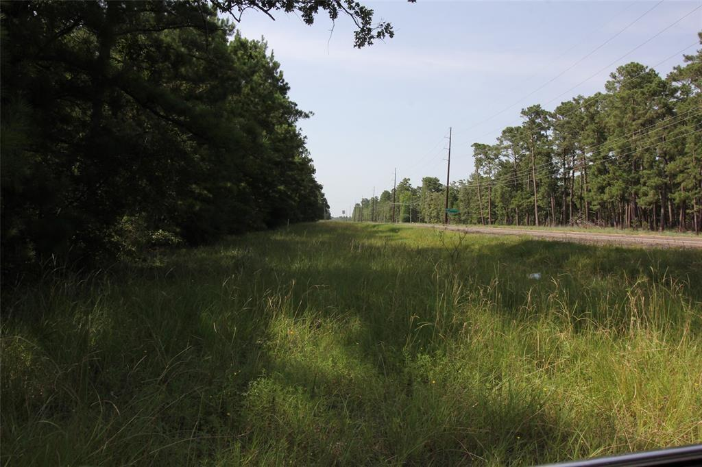 Beautiful wooded acreage with frontage on FM 980. This property is just a couple of miles from Lake Livingston and Waterwood National Golf course.  There are minimal restrictions but lots of room to build your dream home. This property is the remaining tract of a 36+/- acres. Survey shows acreage to be 13.273. Please note , in the photo sections, the survey show specifically which tract is for sale. There are utility easements on the south and west sides of this property. The gate is locked but used by the Waterwood MUD to access their storage tank on the southwest corner of the property. Please do NOT view property without notifying the agent or broker.