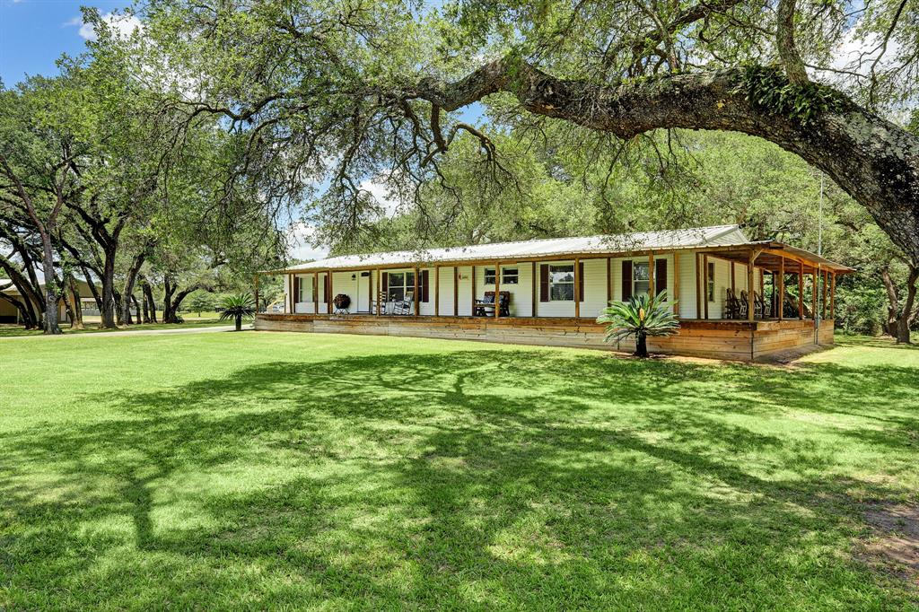 Hunt, fish, explore or just relax on this 32 acre once in a lifetime property less than an hour West of Houston! Includes a 1900 sf covered bridge overlooking a 5 acre lake, a 3200 sf party barn, 15 beautifully groomed acres with large live oak trees throughout, and 1.5 miles of trails winding through 12 acres of native woods adjoining the San Bernard River. The 2000 sf 5 bedroom 2 bath home featuring a wraparound porch, fireplace, and metal roof was completely remodeled in 2011 with 2019 appliances . A paved driveway leads past the home to the covered bridge. You'll want to build your dream home here or just move right in!