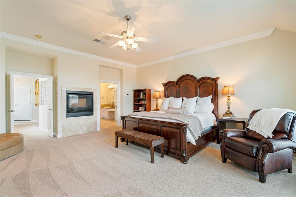 The master suite features a double-sided fire place, crown molding and lots of natural light.